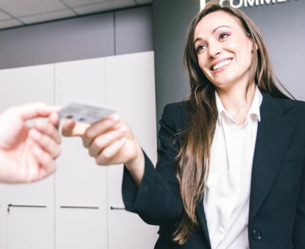 Business woman giving business visit card to her client